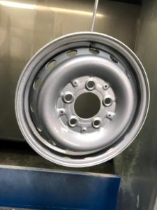 Repaired and refurbished steel alloy wheel with white colour change after