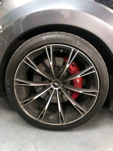 Alloy wheel on car with dent on top of the wheel before